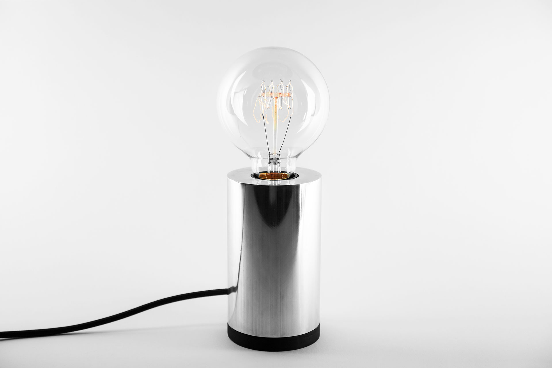 Aluminum table lamp with retro Tesla bulb inspired by masculine minimalist design