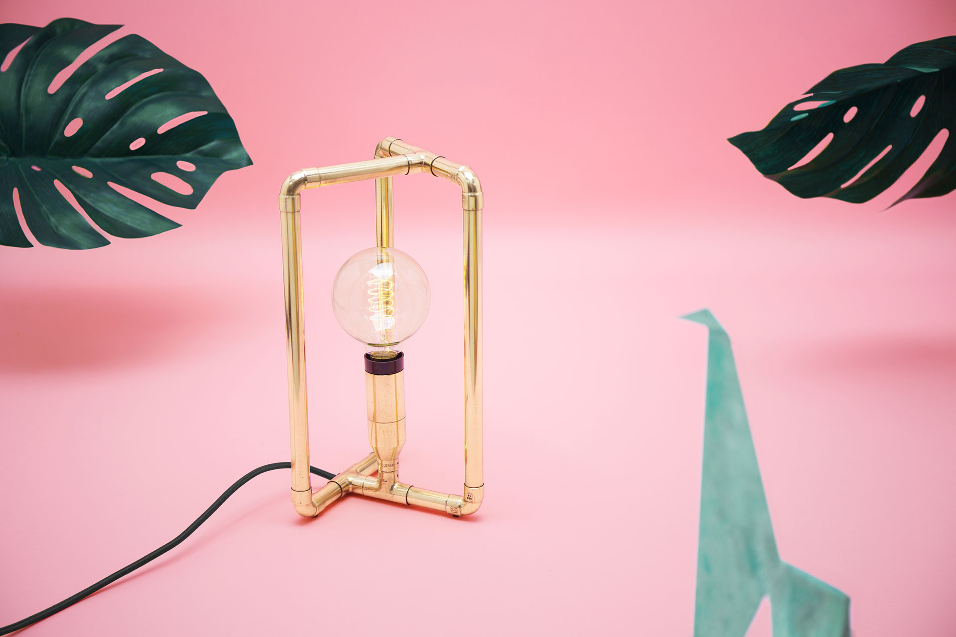 Designer bedside lamp in modern brass with creative touch dimmer and retro bulb in millennial pink apartment