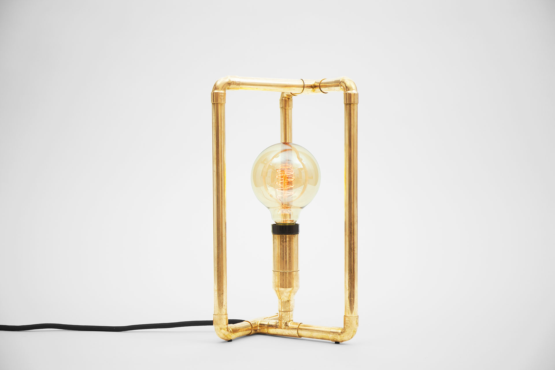 Small bedside lamp in gold brass metal finish with retro Tesla bulb inspired by modern minimalist design