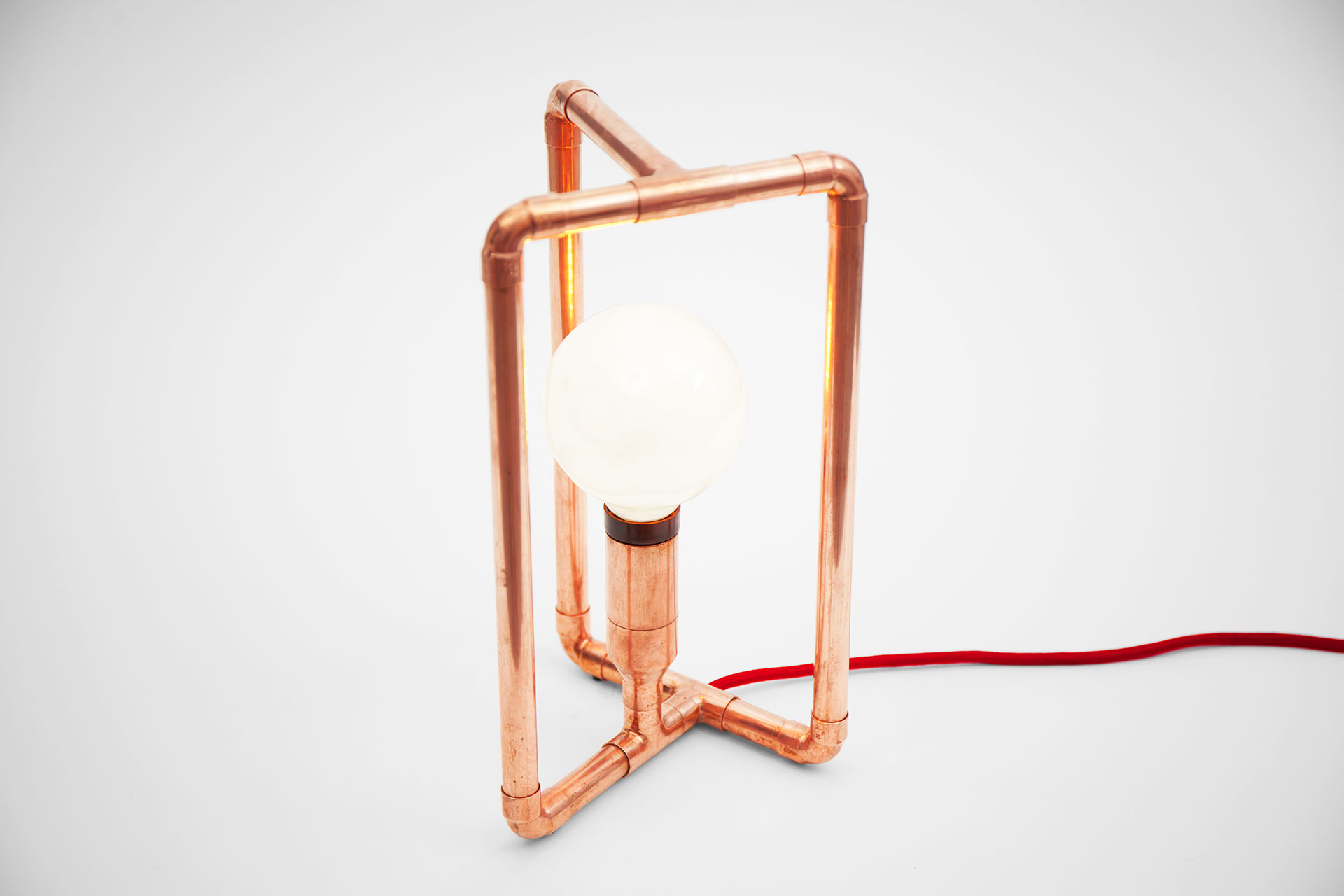 Geometric design desk lamp made of copper tubing with red braided cord inspired by 3D Möbius strip