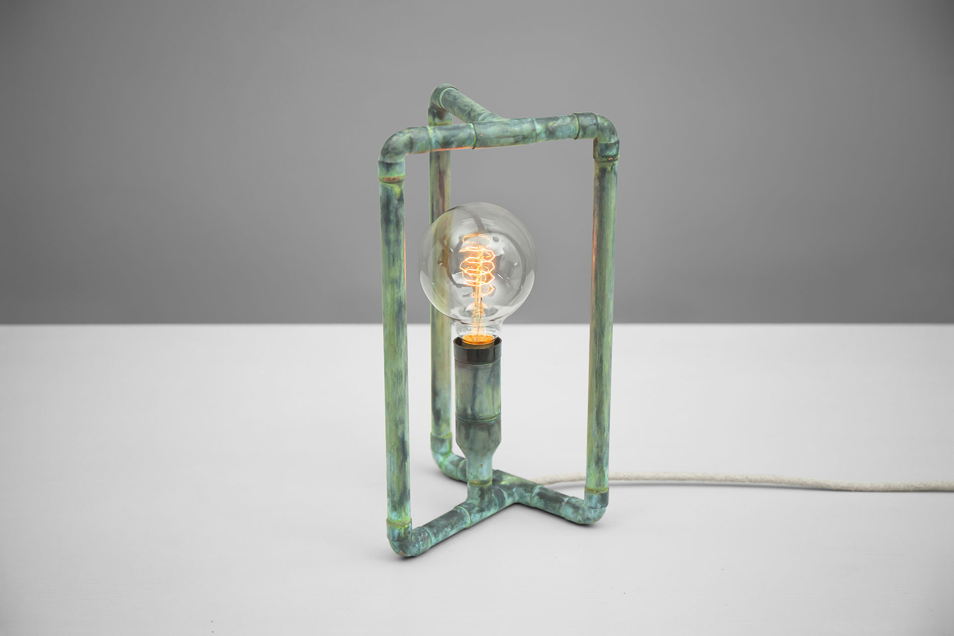 Conceptual design table lamp in handmade green patina metal finish with creative touch dimmer and retro bulb