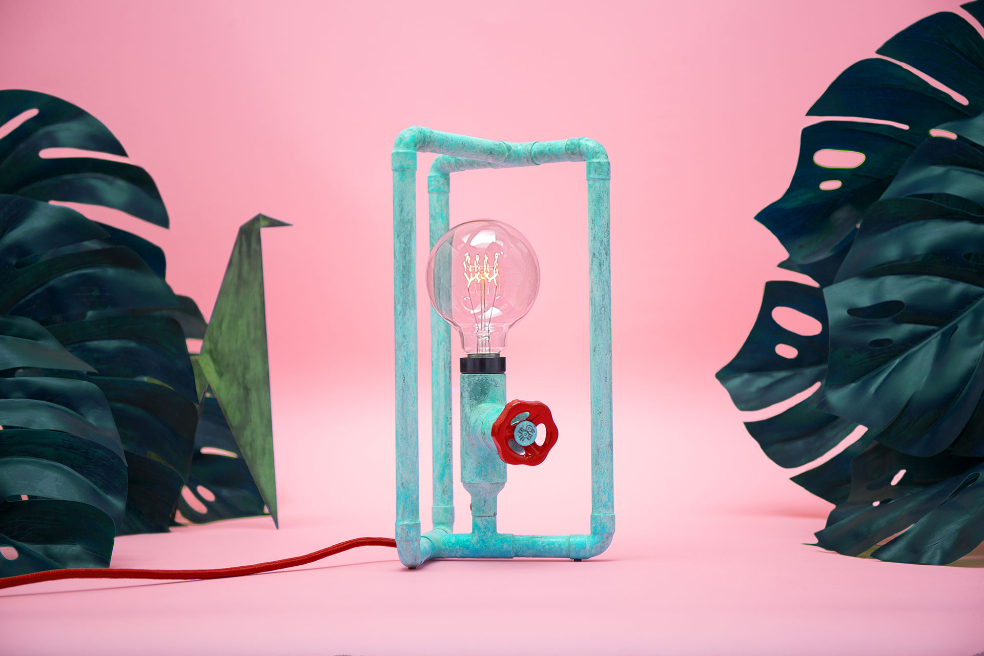 Fun design table lamp in trendy turquoise patina with colorful knob dimmer in millennial pink apartment