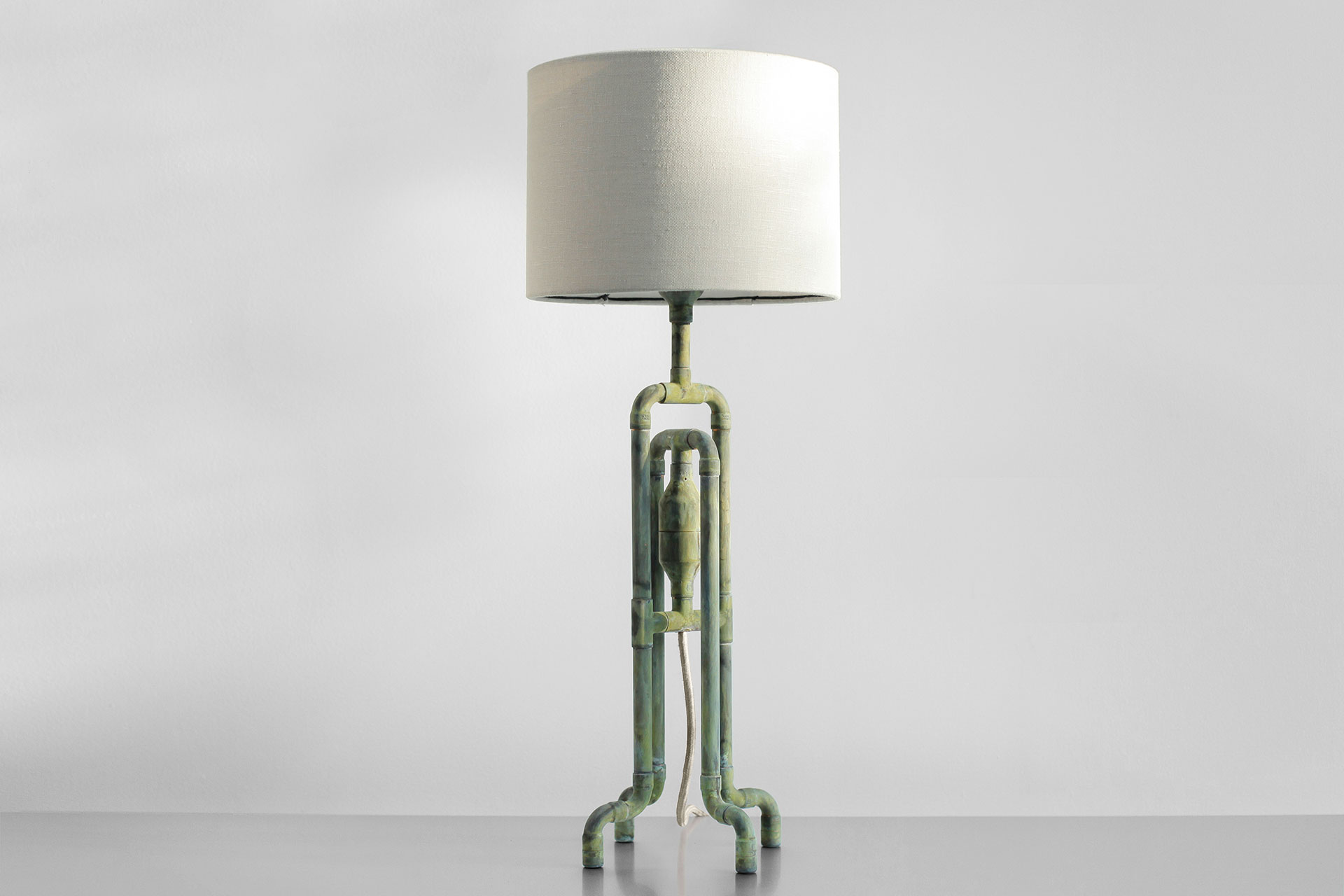 Trendy green patina table lamp with natural linen shade in modern masculine apartment