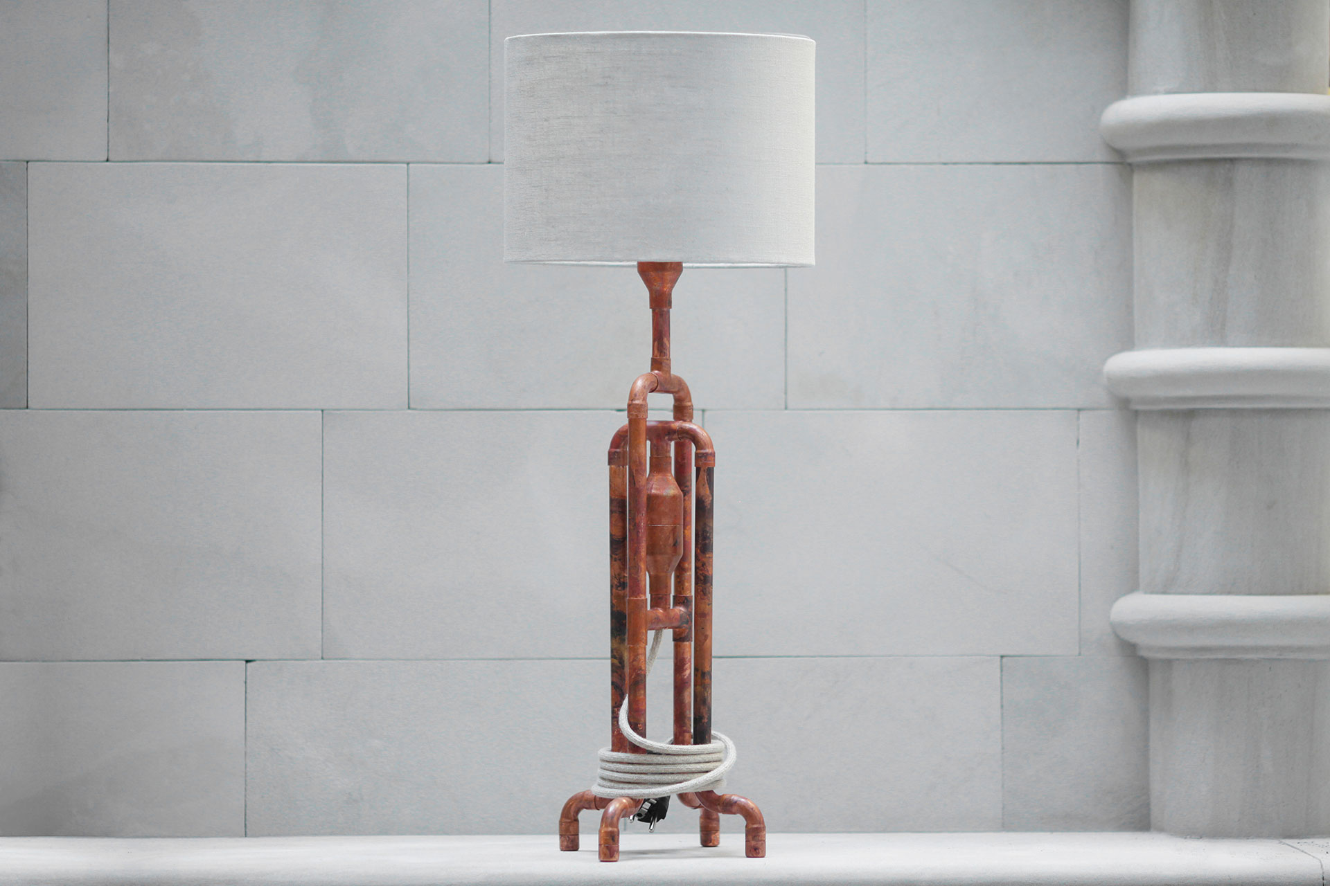 Designer table lamp in aged copper patina with natural linen shade inspired by loft design
