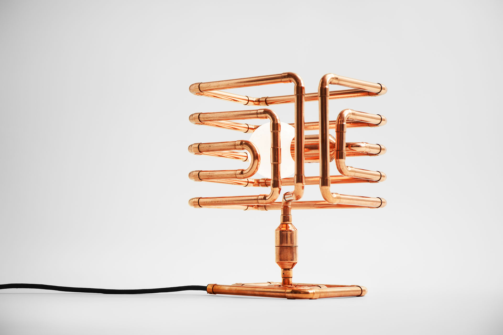 Futuristic design table lamp in trendy copper metal finish inspired by conceptual pipe art
