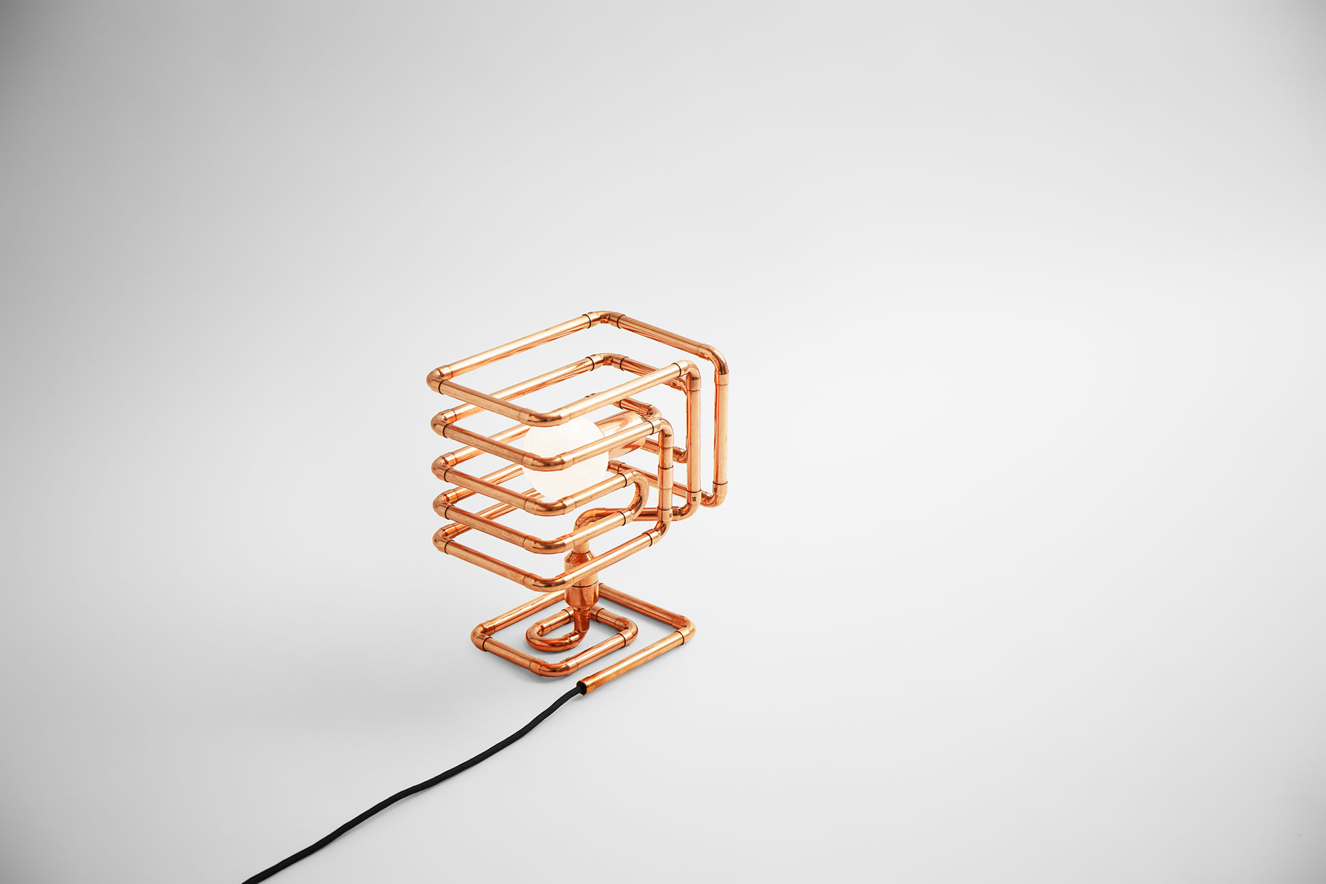 Designer table lamp in modern copper metal finish inspired by industrial sculpture art