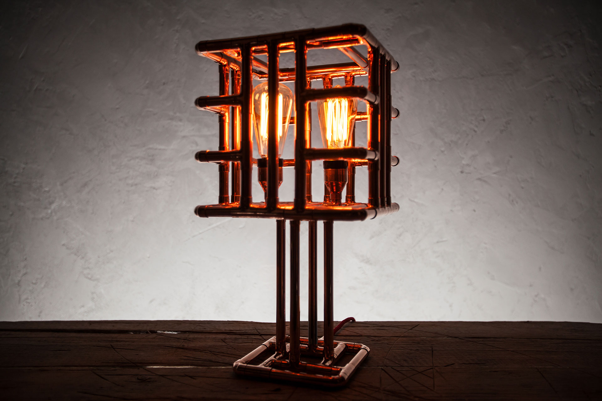 Industrial cage table lamp made of copper pipes with vintage Edison bulbs