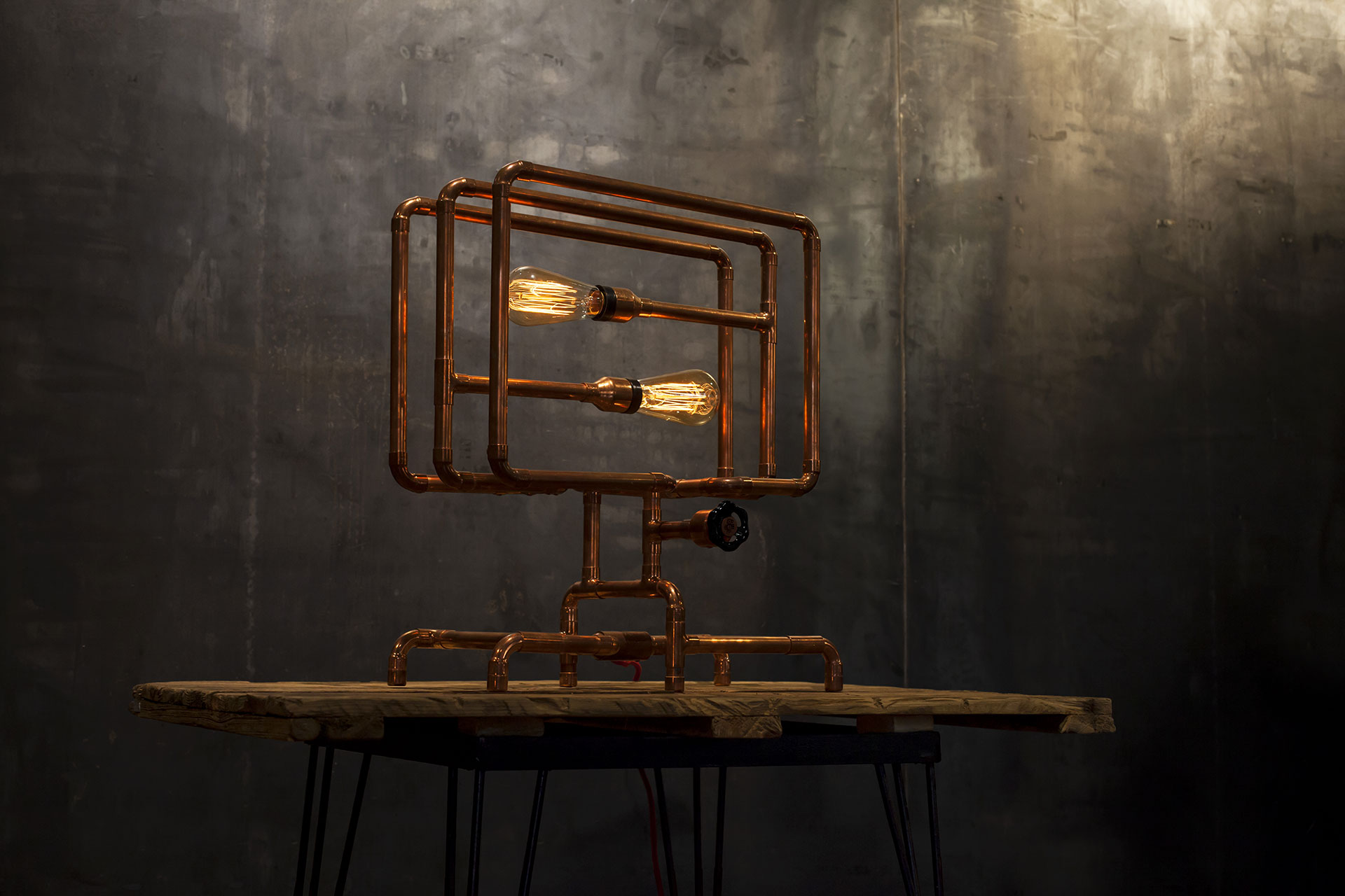 Dimmable copper pipe table lamp inspired by steampunk design on vintage loft console table
