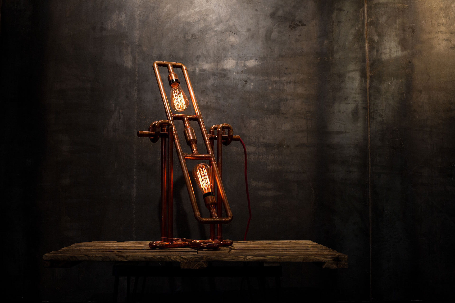 Copper pipes table lamp with vintage Edison bulbs in loft style interior