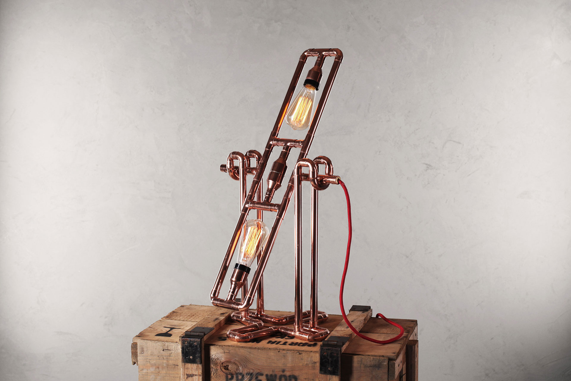 Steampunk table lamp made of copper pipes on a vintage army chest box