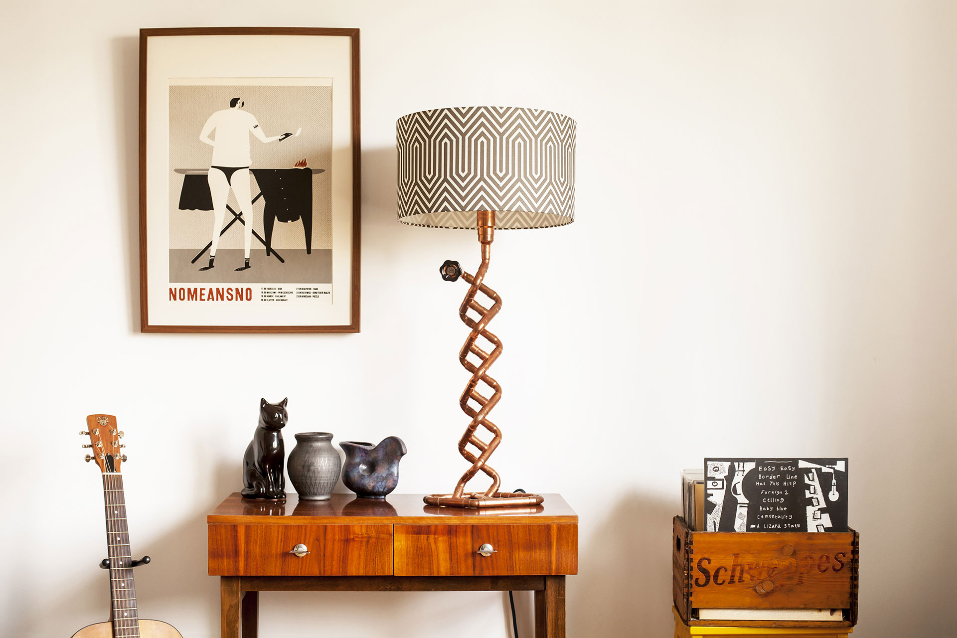 Copper tubing table lamp with custom geometric shade in vintage modern apartment