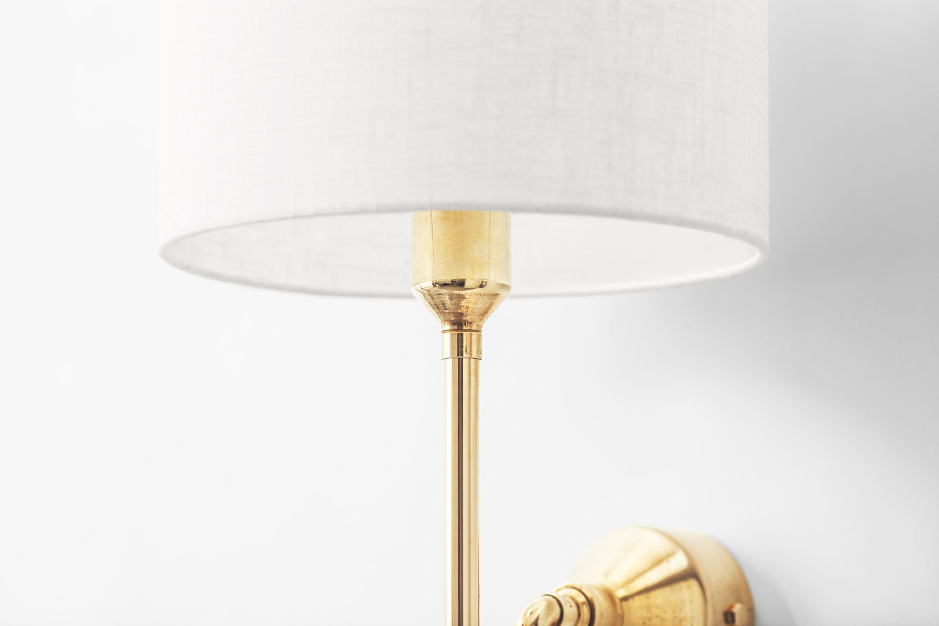 Contemporary bedside sconce in brass with white linen shade