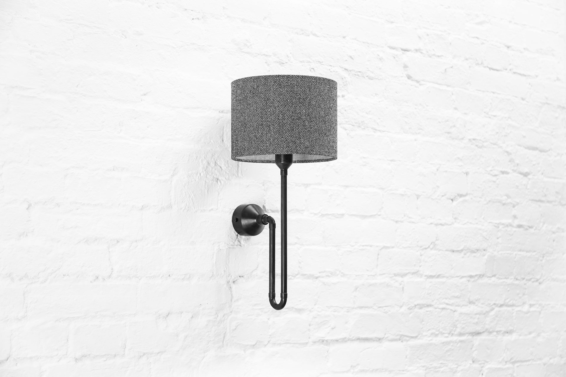 Black patina sconce with herringbone shade in chic apartment