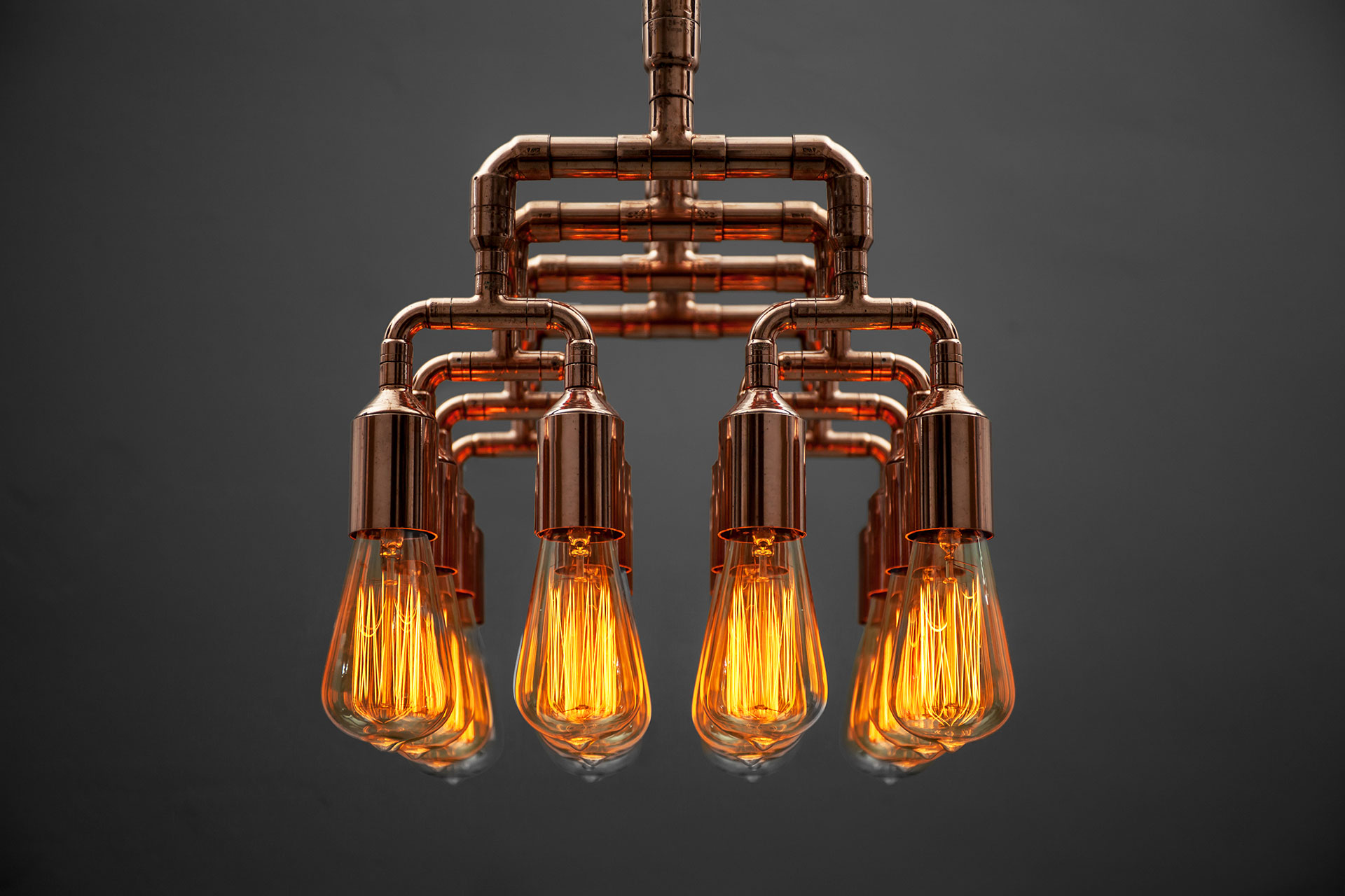 Steampunk design chandelier made of copper pipes with vintage Edison bulbs