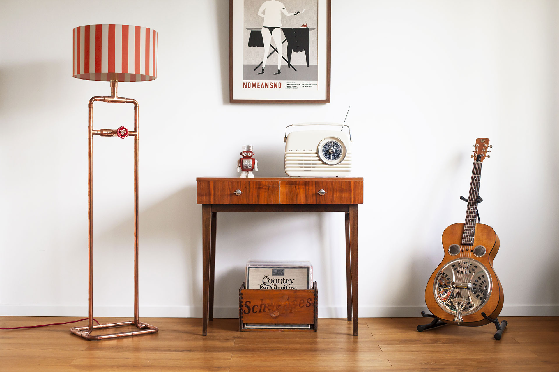 Industrial style copper tubing floor lamp with knob dimmer and stripe shade in cozy hip apartment