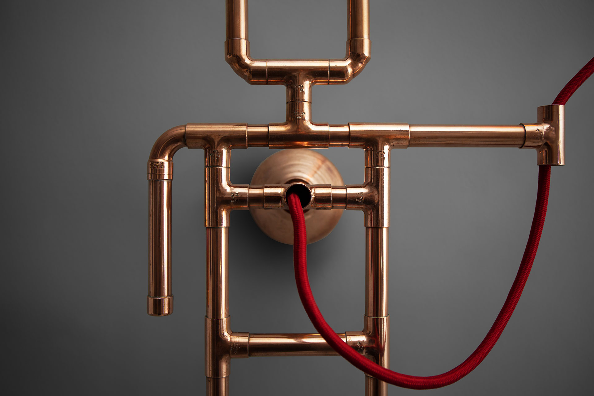 Copper pipe wall lamp with red braided cord