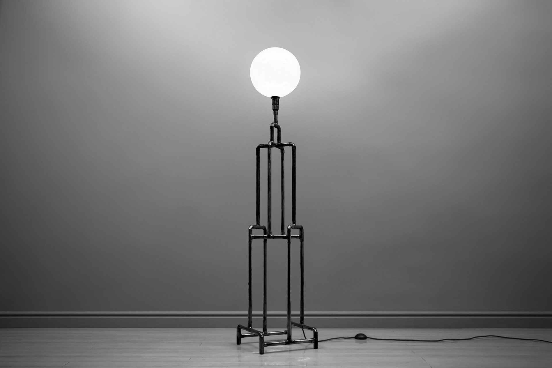 Industrial design floor lamp in black metal with milk globe inspired by Art Deco architecture