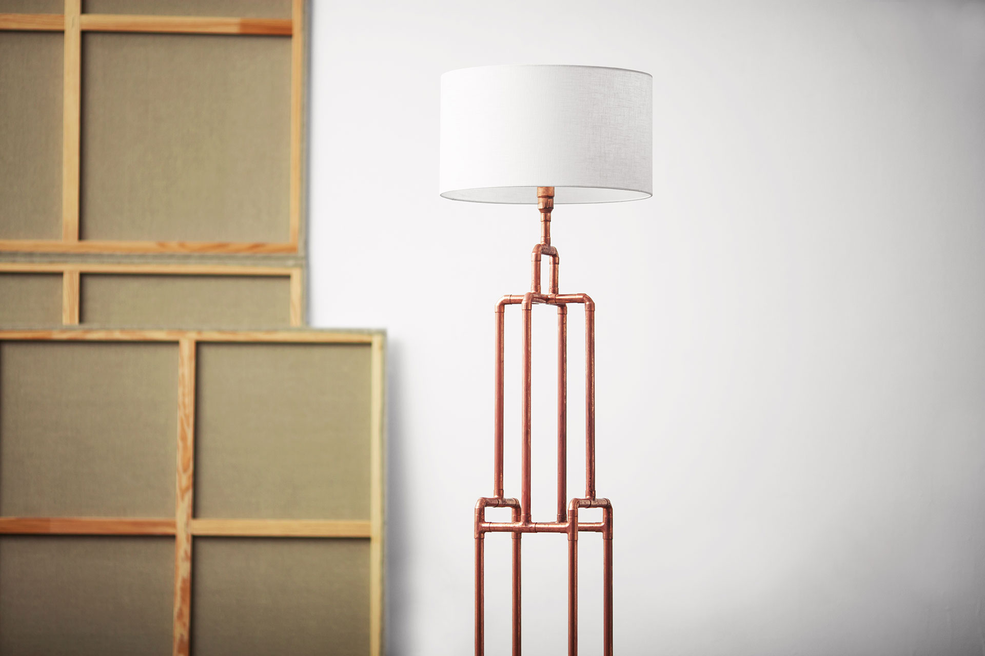 Designers floor lamp made of trendy copper pipes with natural white linen shade