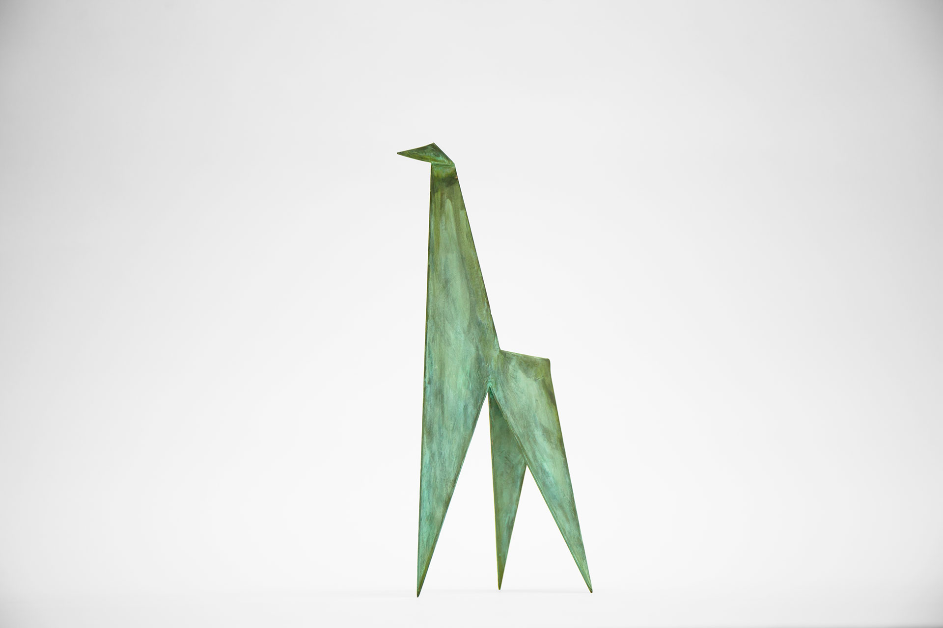 Metal origami sculpture in green patina inspired by modern conceptual art