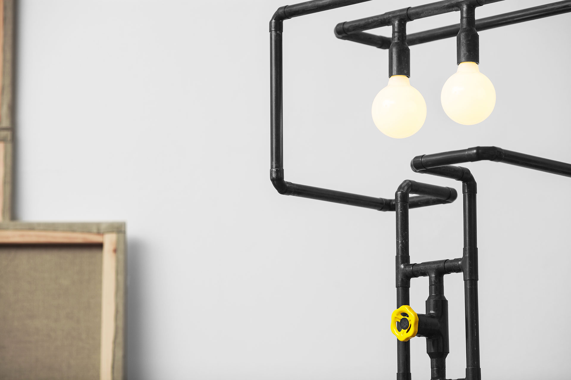 Funny dimmable floor lamp with yellow knob made of copper pipes in natural black patina