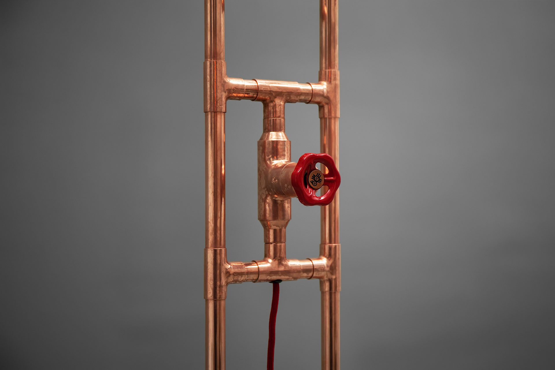 Red knob dimmer in loft style floor lamp made of copper tubing
