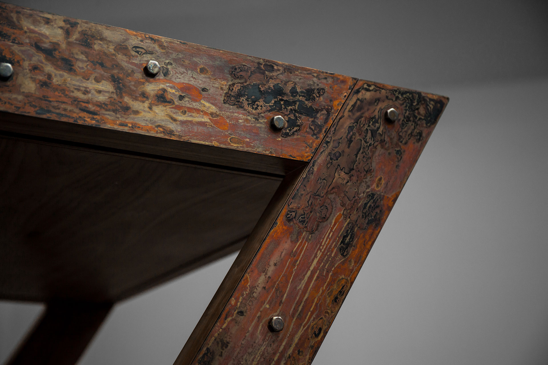 Aged copper finish with rust metal look on brutalist desk