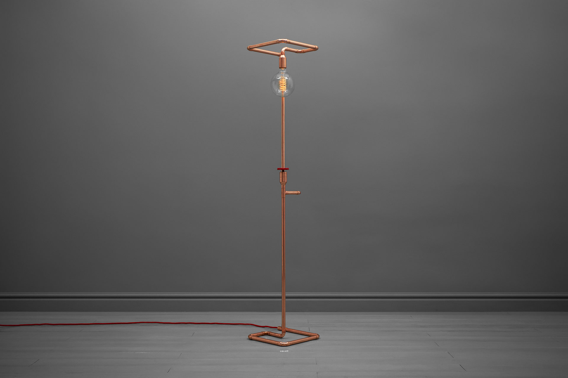 Unusual floor lamp in trendy copper or modern brass inspired by industrial pipe design
